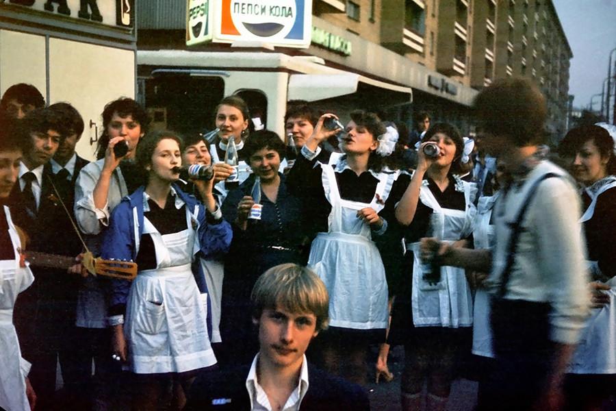 Adolescentes celebram a formatura com uniformes típicos russo-soviéticos tomando Pepsi. Moscou, 1981.