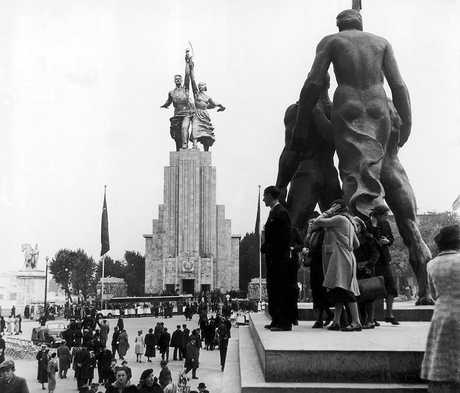 Penampakan monumen Buruh dan Perempuan Kolkhoz (depan) karya Vera Mukhina dan Paviliun Pusat (belakang) dari sisi Prospekt Mira, 1959. Mukhina sangat tak puas dengan penempatan patung ini.