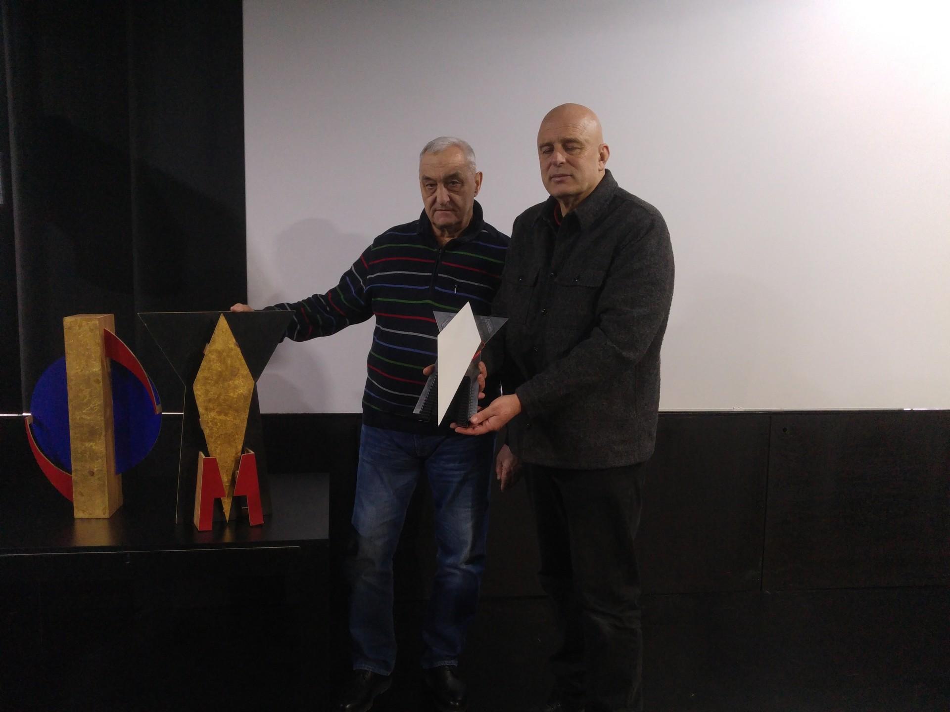 Dmitrij Dragun (Akademija Ciolkovskega) in Dragan Živadinov z maketo prvega umetniškega satelita in znakom pokojne igralke Milene Grm.