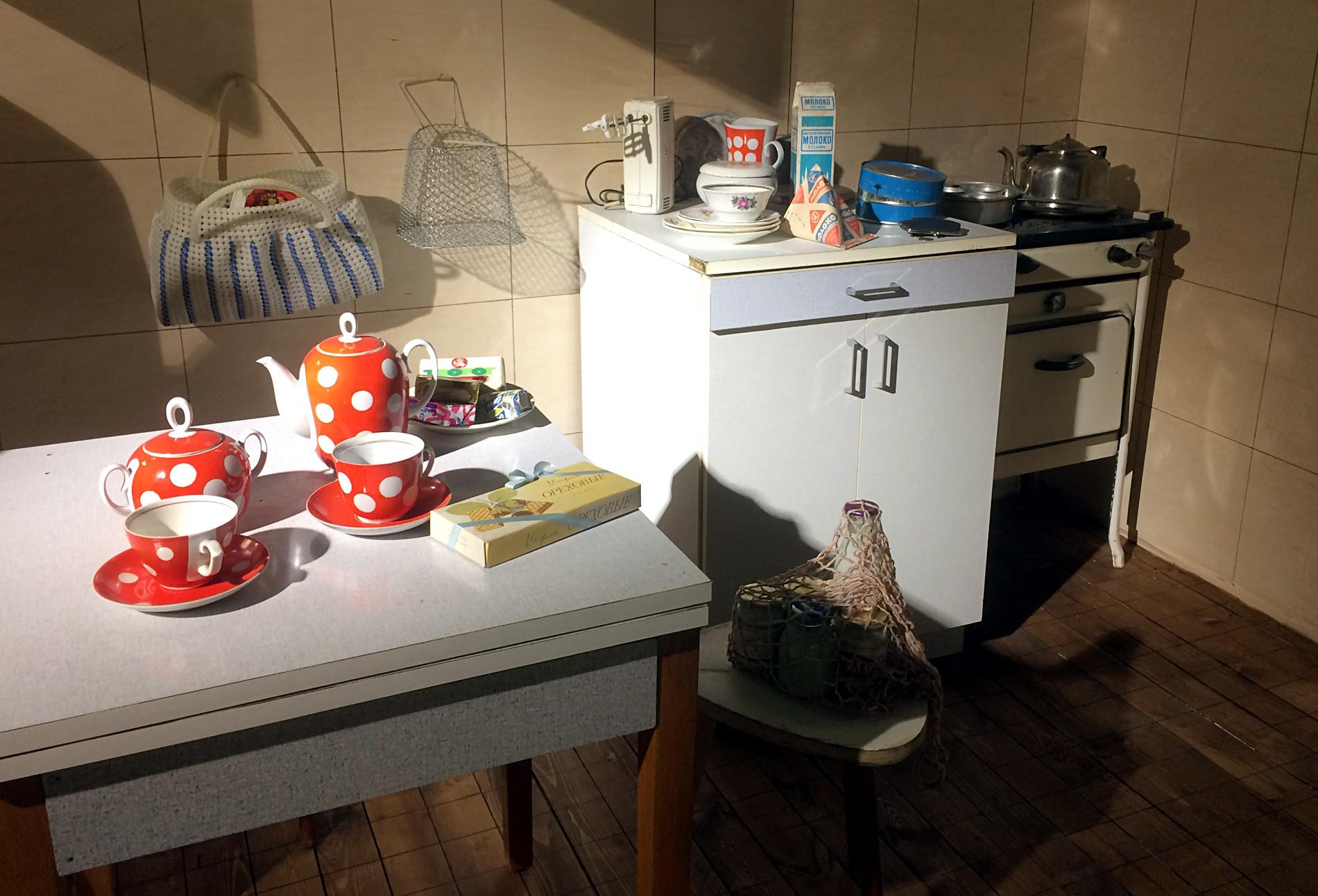 Kuhinja iz 70. let 20. stoletja. Na mizi tipični čajni servis, ki ste ga našli po vsej Sovjetski zvezi, na hladilniku sovjetsko mleko v trikotni embalaži, na tleh pa