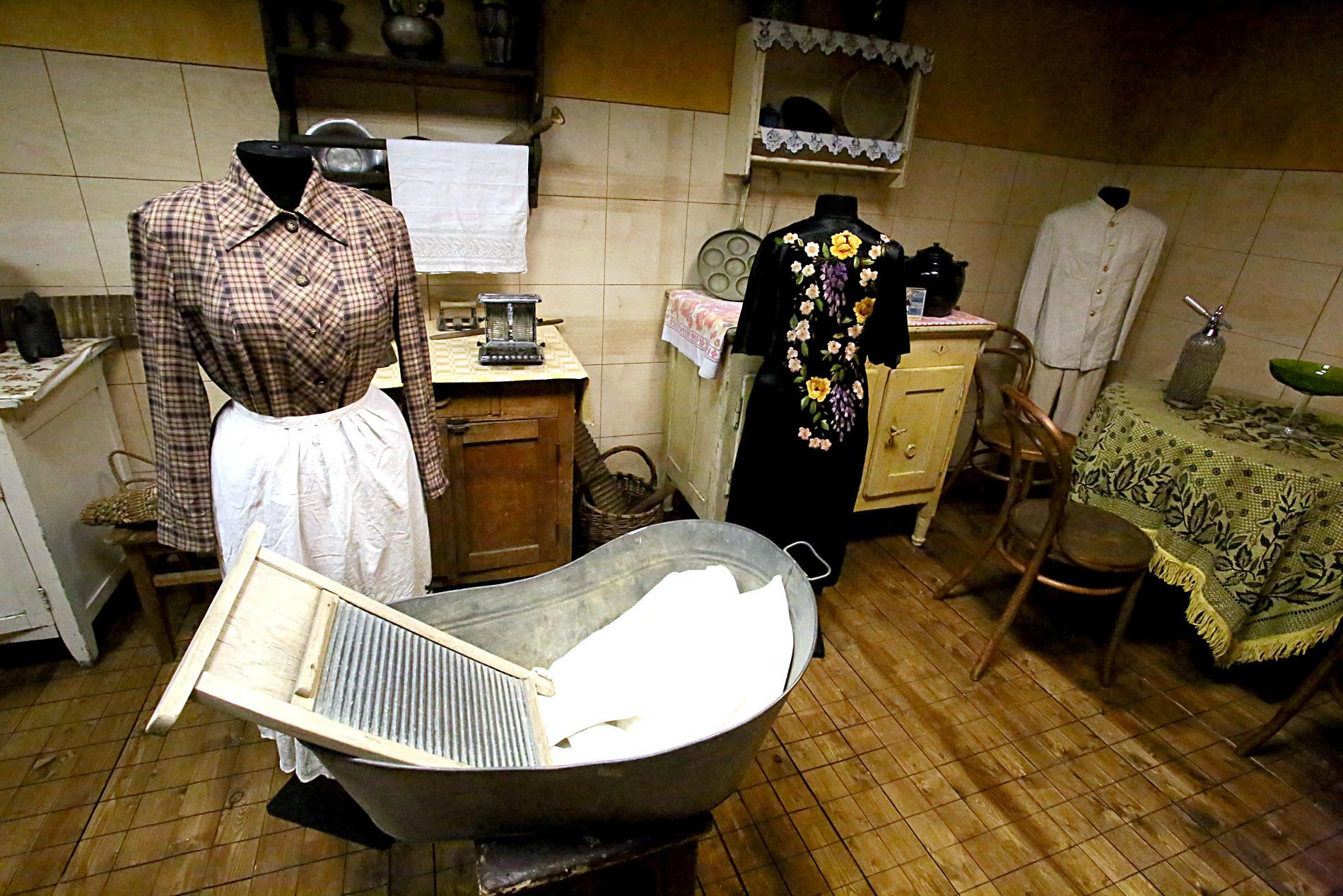 Kuhinja iz 40. let 20. stoletja. Na levi omarici ročna masažna naprava, ki je prišla prav zlasti za valjanje testa, poleg pa pekač za kruh; v košari valjar in pripomoček za drgnjenje perila pri pranju; na desni omarici ponev za jajca ali palačinke; na mizi zopet sifon.