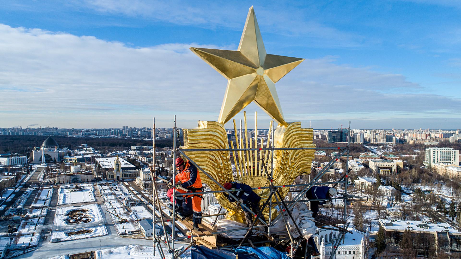Operai al lavoro per restaurare la stella d'oro nel padiglione centrale del parco VDNKh di Mosca