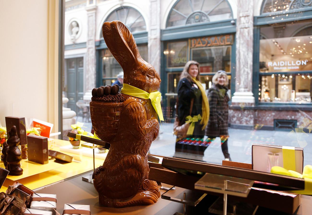 Dua perempuan berjalan melewati cokelat kelinci Paskah di toko pembuat cokelat Belgia Neuhaus di Brussel.