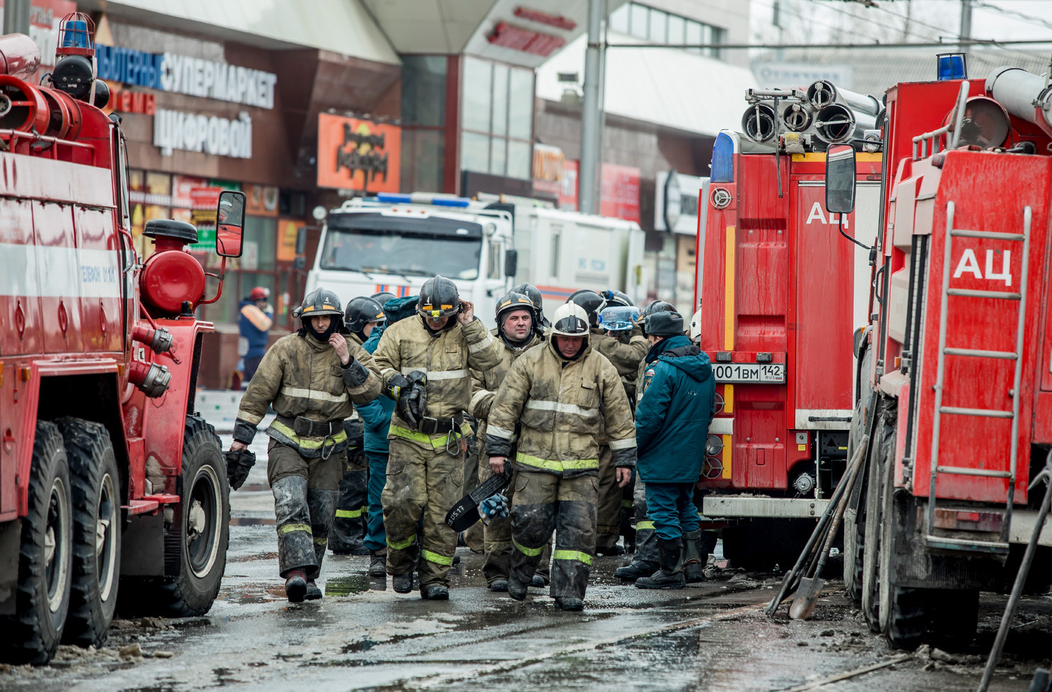 A group of firefighters walk near the scene of the shopping center after a fire on March 26, 2018.