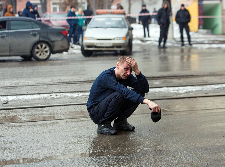 """Hombre junto al centro comercial """"Zímniaia Víshnia"""" en Kémerovo, el 25 de marzo de 2018."""