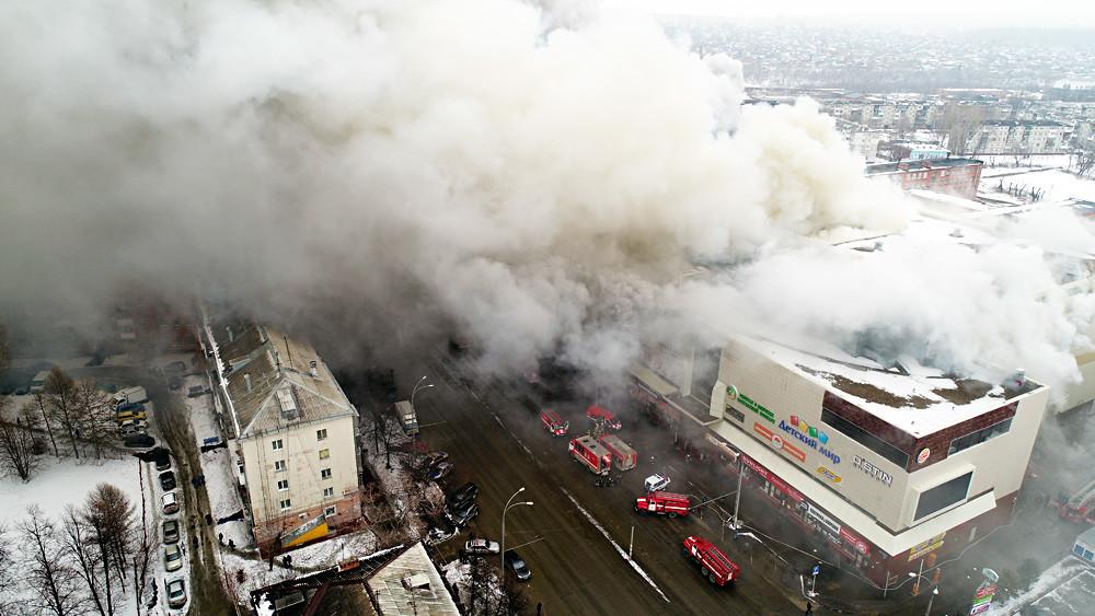 Asap tebal membubung di atas pusat perbelanjaan bertingkat di kota Kemerovo pada 25 Maret 2018.