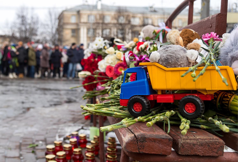 Karangan bunga, lilin, dan mainan dari warga kota yang berduka di luar pusat perbelanjaan Zimnyaya Vishnya.