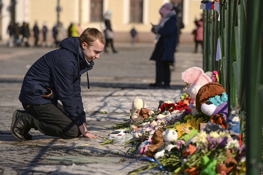 A man kneels near a spontaneous memorial on Dvortsovaya Square in St. Petersburg.