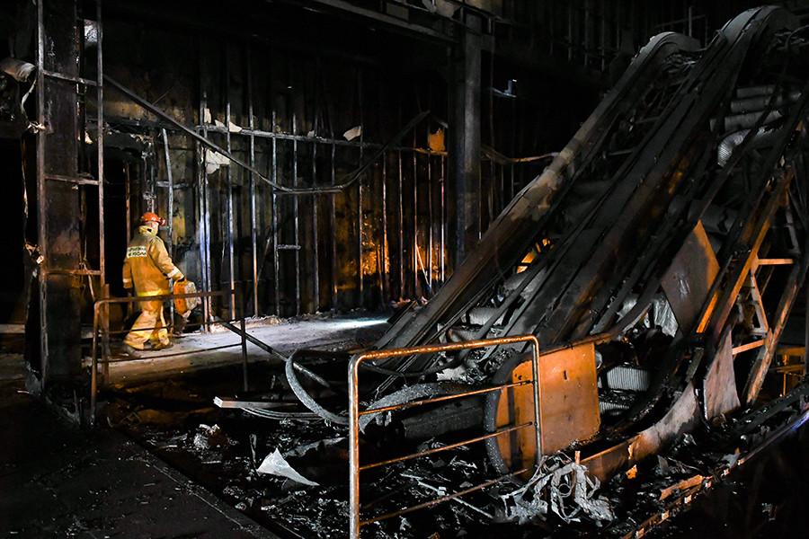 Funcionário do Ministério para Situações de Emergência da Rússia em meio aos escombros de shopping incendiado