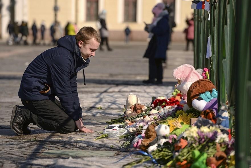Moški v počepu poleg spontano nastalega mesta za poklon žrtvam, trg Dvorcovaja, Sankt Peterburg.