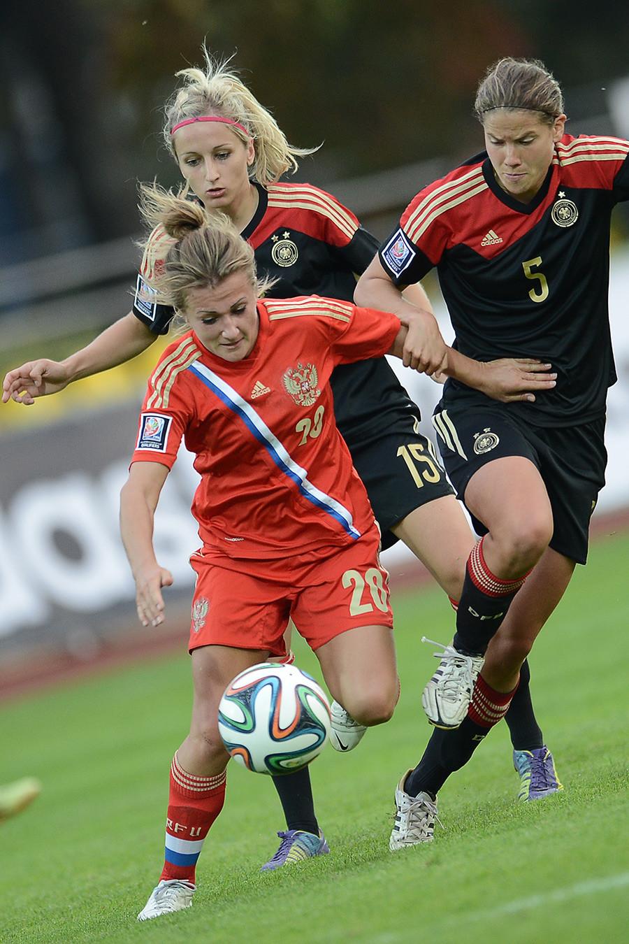 Jogo de qualificação entre Alemanha e Rússia para Copa do Mundo Feminina 2015. Da esq. para dir.: Nelli Korovkina (Rússia), Kathrin Hendrich (Alemanha) e Annike Krahn (Alemanha).