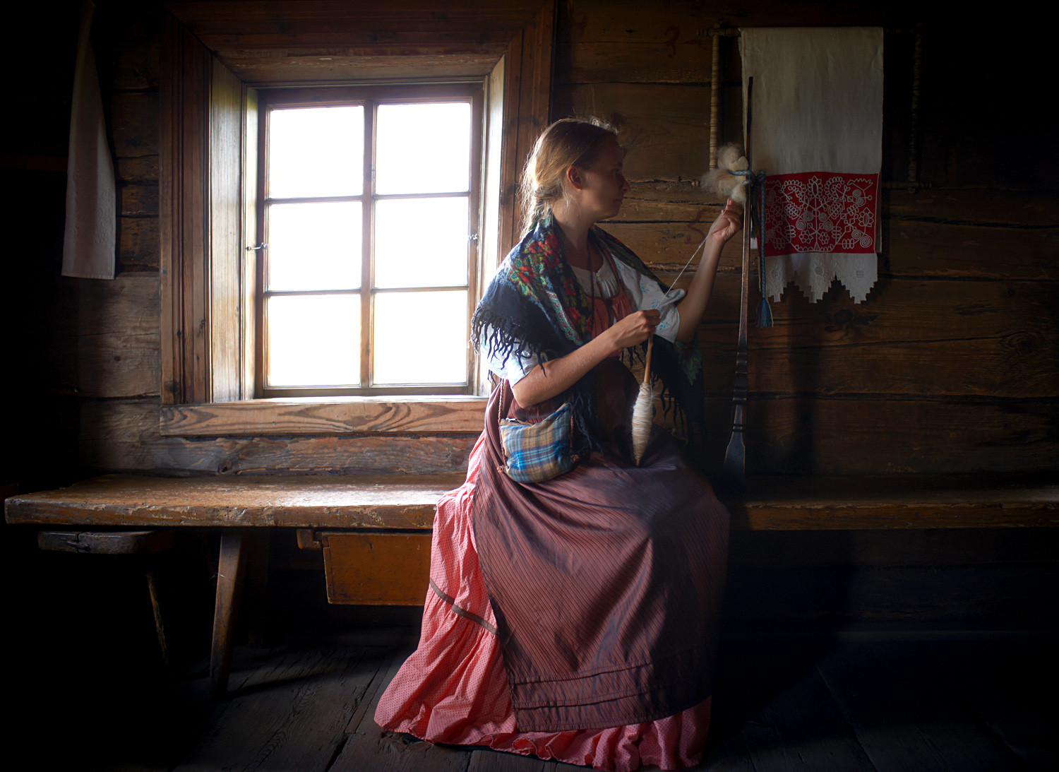 A woman in national clothes spinning yarn in the Kizhi State Historical-Architectural and Ethnographic Museum Reserve.