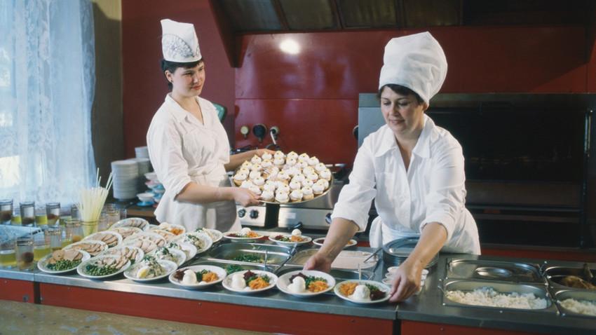 Koki-koki kantin pekerja di pabrik produksi makanan bersiap menyediakan makanan untuk para buruh, 1986.