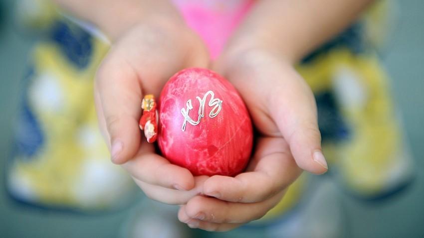 Dekle drži velikonočno jajce na predvečer pravoslavne velike noči v Katedrali Donske Božje matere.