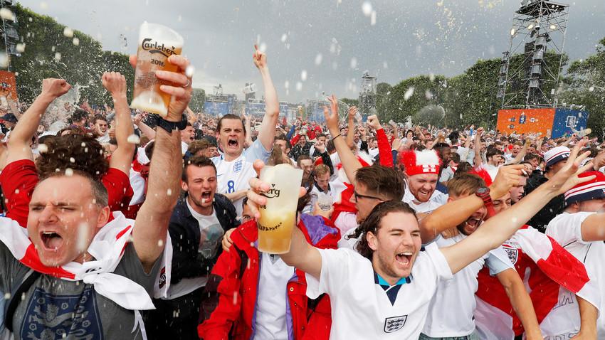 Hinchas ingleses celebran un gol mientras toman cerveza.