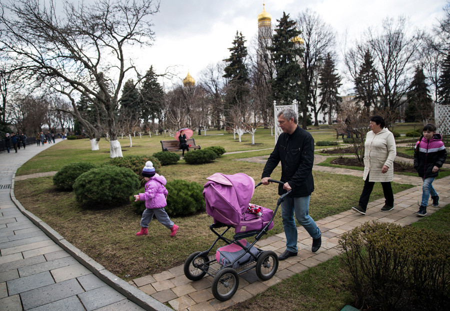 A family walk inside the Kremlin with the Ivan the Great Bell Tower in the background, in Moscow.