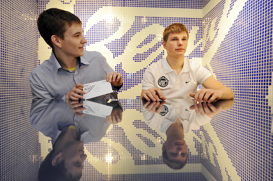 Footballer Andrei Arshavin (R) signs autographs during his meeting with fans at a FC Zenit outlet shop