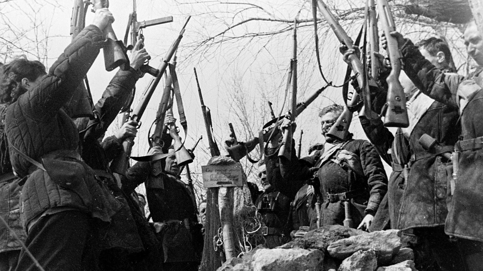 Guerrillas swearing to revenge for their comrade killed by the Nazis near his tomb.