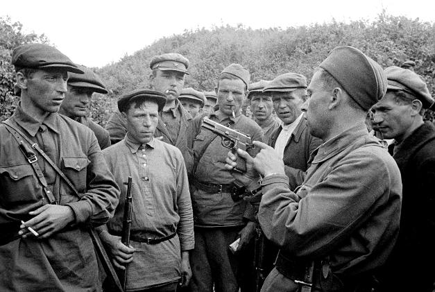 Partizanski poveljnik uči svoje vojake uporabljati orožje.