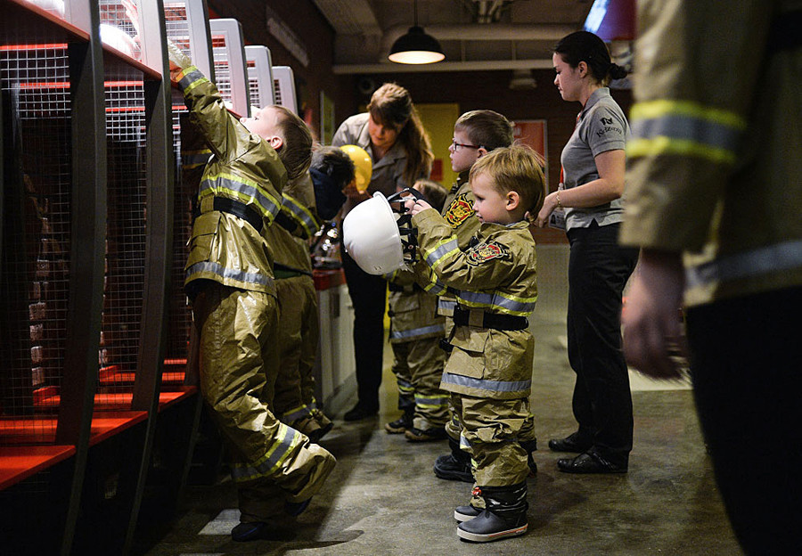 Children learning fire-extinguishing skills at the fireman area of the Kidzania game training park in Moscow.