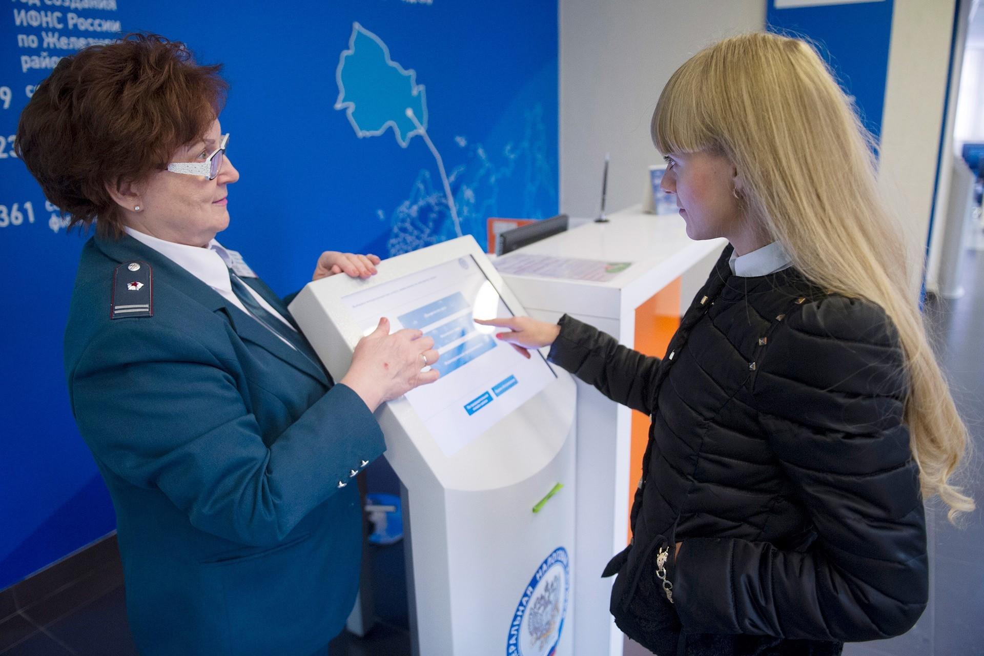 Ženska uporablja elektronski terminal v pisarni ruske davčne uprave Centralnega okraja v Novosibirsku.