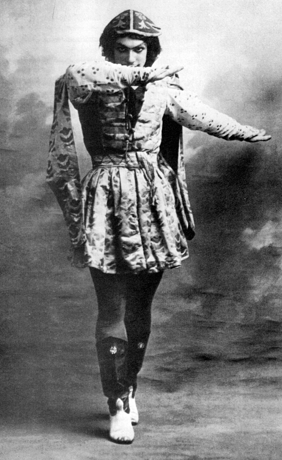 Vaslav Nijinsky (1889-1950) was a Russian ballet dancer who is often cited as the greatest male dancer of the early 20th century. Here he is wearing high boots and a long tunic, peering above his right arm, left arm extended to the side in the Grand pas classique hongrois from Le festin.