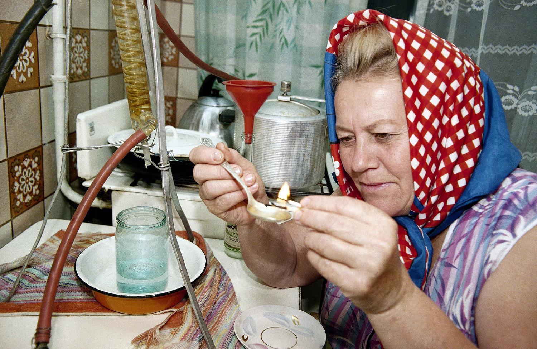 Russa na cidade de Maikop, no sul do país, acende com fósforo colher cheia de destilado caseiro elaborado por ela para testar sua qualidade