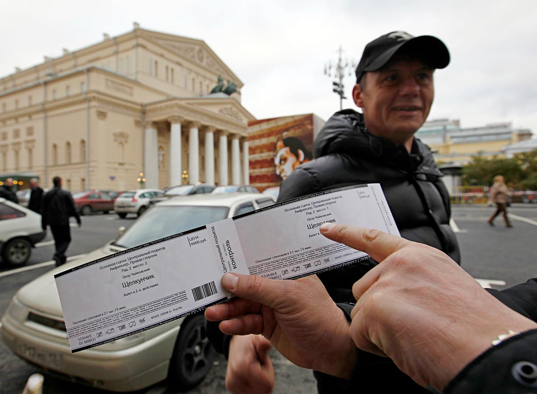 Moški pred gledališčem Bolšoj ponuja vstopnico za predstavo Hrestač Petra Iljiča Čajkovskega.