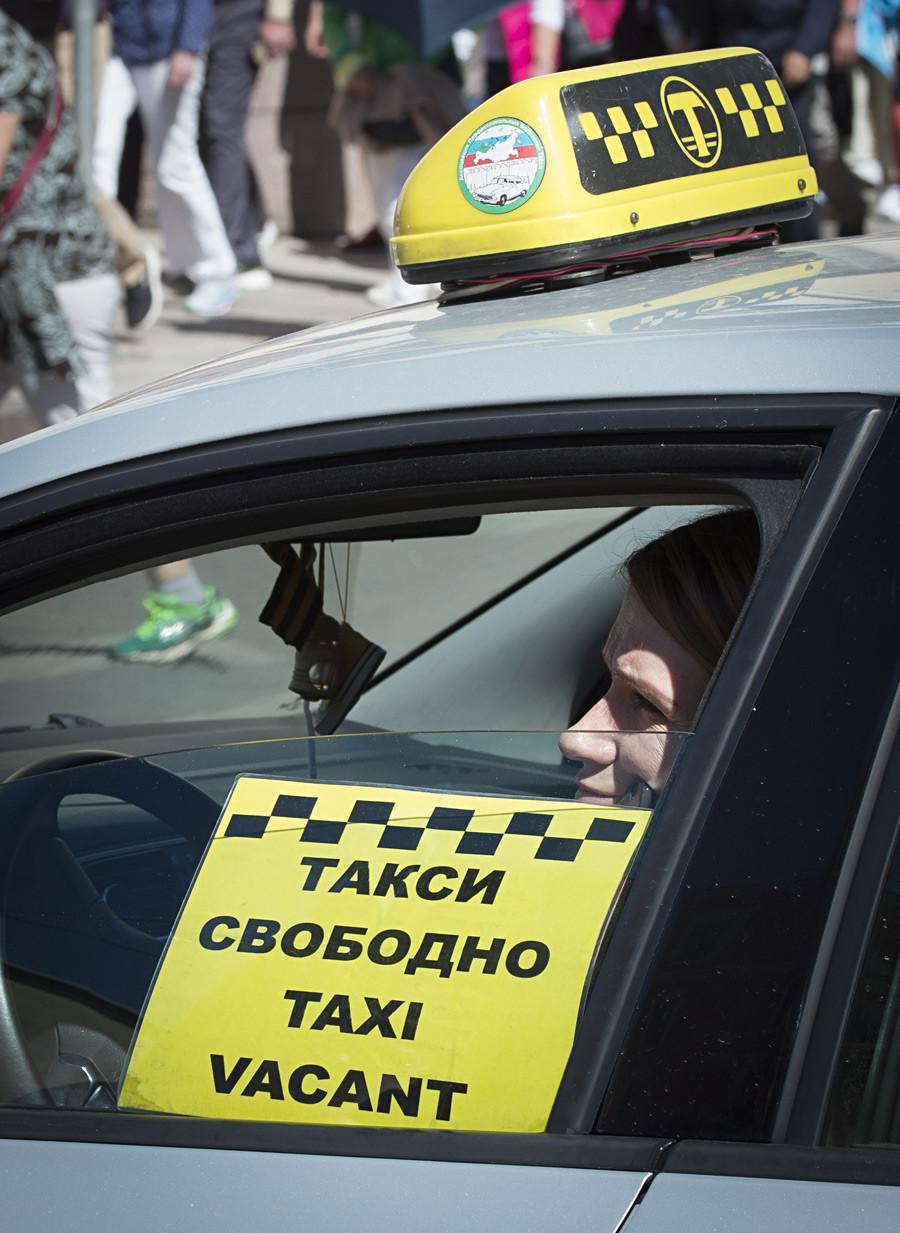 Taksist čaka na stranke v Sankt Peterburgu.