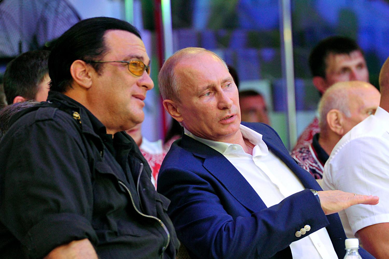 Председник Русије Владимир Путин и амерички глумац Стивен Сигал посматрају прво руско национално првенство у мешовитим борилачким вештинама у Сочију. 11. август 2012. године.