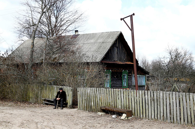 Ivan Chamianok, 90 anos, sentado em frente a sua casa na vila de Tulgovitchi, na Bielorrússia