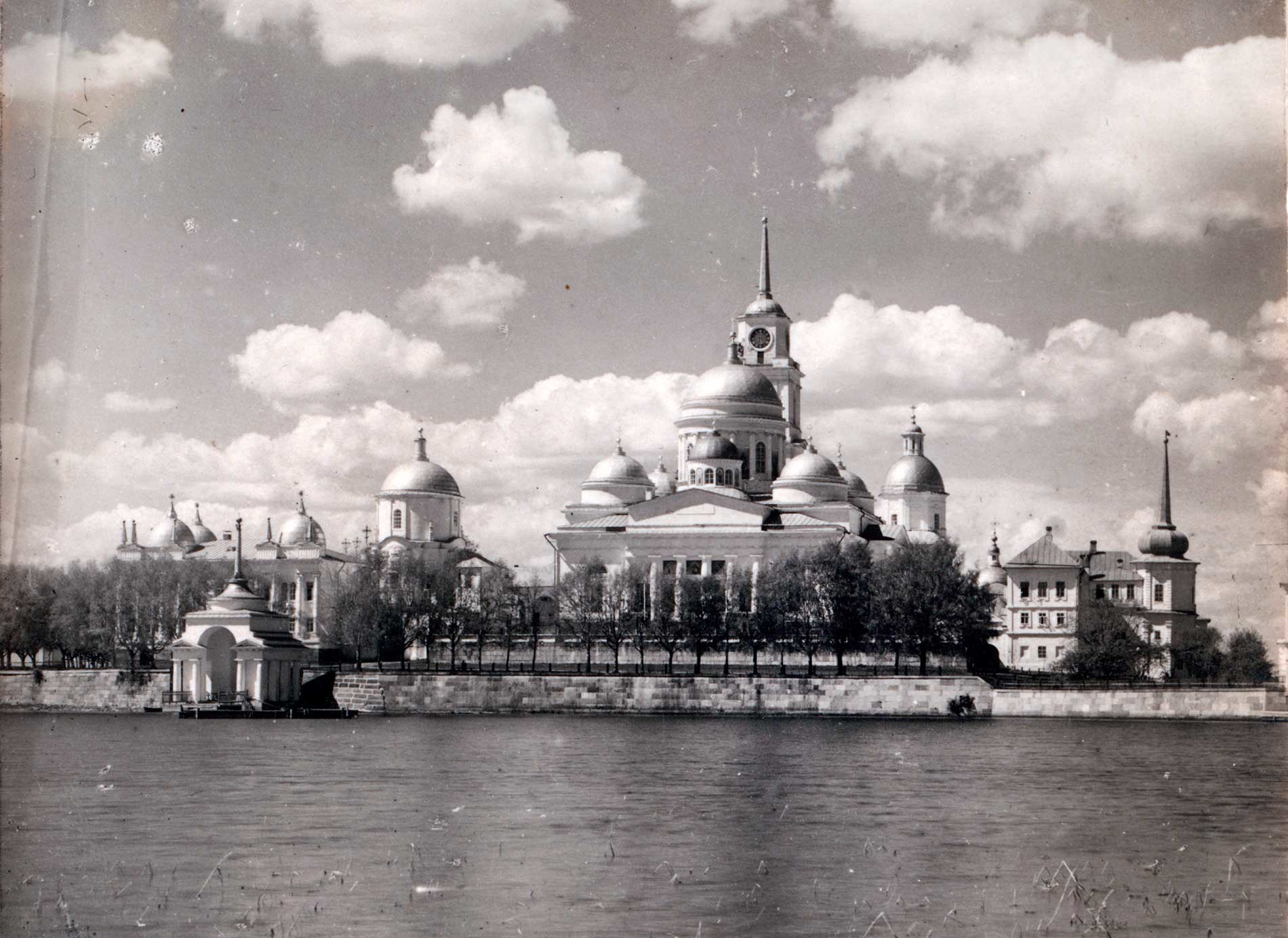 Nilova Pustyn, east view from small island. From left: Archbishop's Landing, Archbishop's Chambers, Church of St. Nilus Stolobensky over East Gate, Epiphany Cathedral&bell tower, Church of SS. Peter&Paul over West Gate, Church of All Saints, Refectory. Summer 1910.