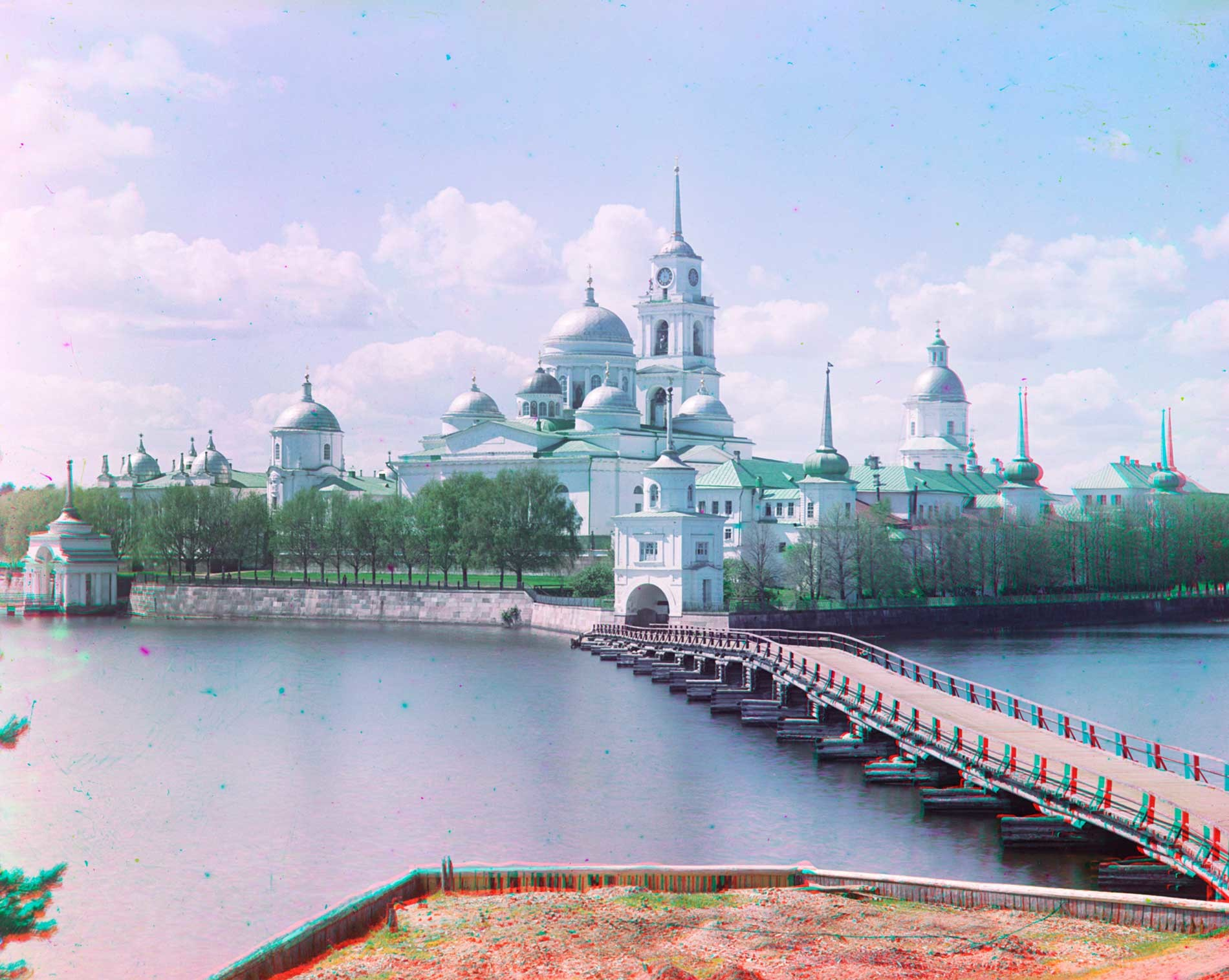 Nilova Pustyn, northeast view from Svetlitsa village. From left: Archbishop's Landing, Archbishop's Chambers, Church of St. Nilus over East Gate, Epiphany Cathedral&bell tower, Svetlitsa Tower, Refectory, Church of SS. Peter&Paul over West Gate. Summer 1910.