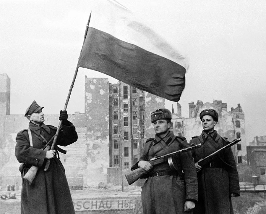 Poljski vojak (levo) in sovjetska vojaka dvigujejo zastavo nad osvobojeno Varšavo, 17. januar 1945.