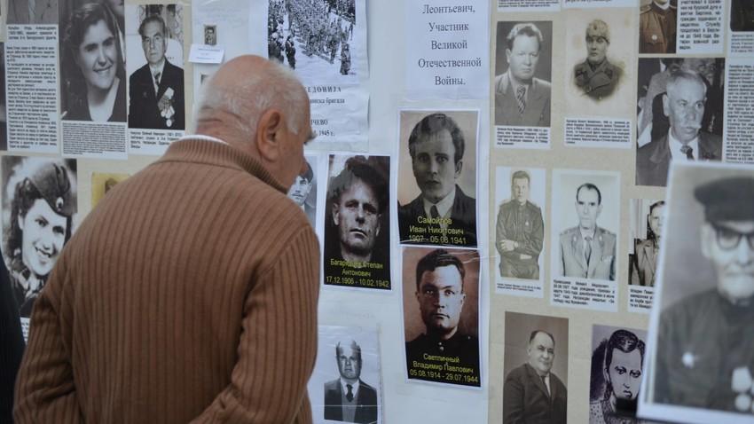 """Граѓанин на Скопје ги гледа фотографиите на """"Ѕидот на сеќавањето"""", изложба во рамките на манифестацијата """"Бесмртниот полк"""", 2017."""