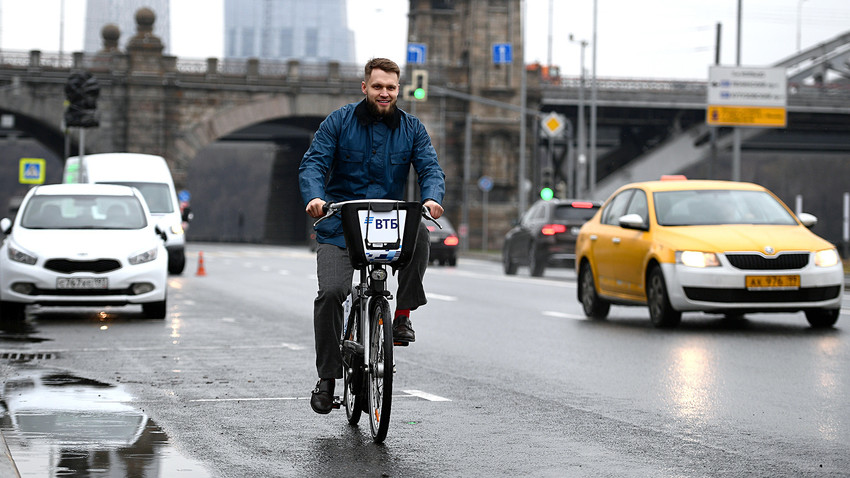 A young man rides a public bike on a Moscow street.