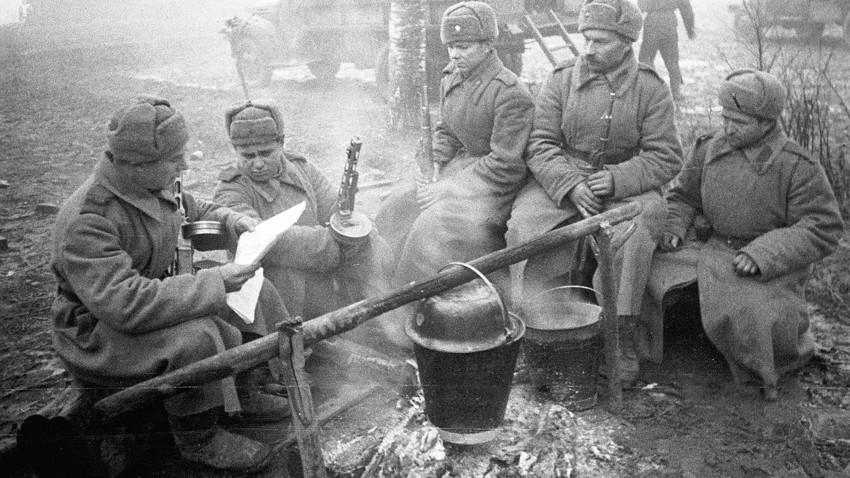 Sovjetski vojaki kuhajo obrok, berejo časopis in se grejejo ob ognju.