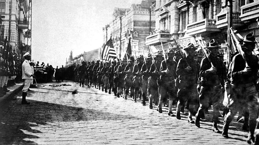 Tropas americanas desfilando em Vladivostok, no Extremo Oriente, sob os olhares de fuzileiros navais japoneses