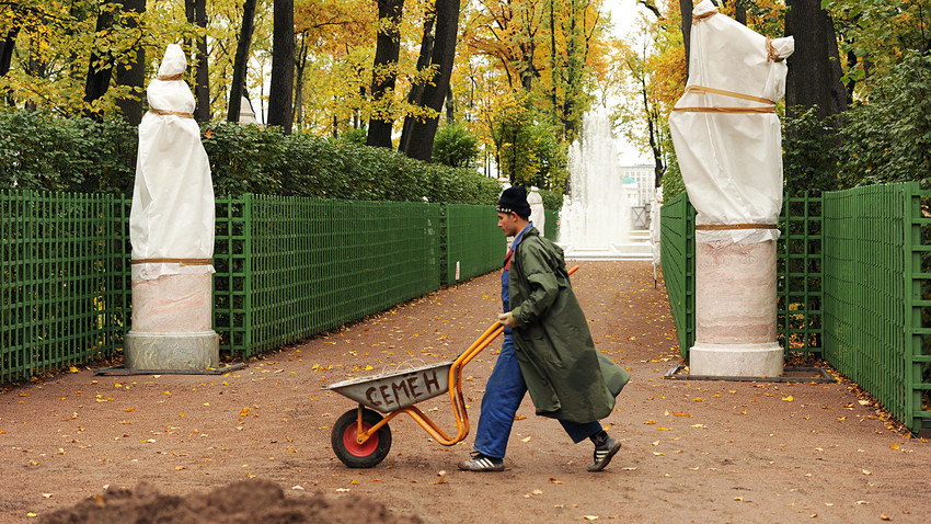 Общински работник почиства падналите листа в Лятната градина в Санкт Петербург