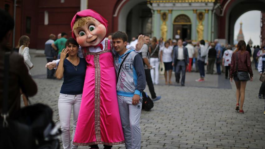Dua orang turis berfoto bersama tokoh serial animasi Rusia, Masha, di Lapangan Merah, Moskow.