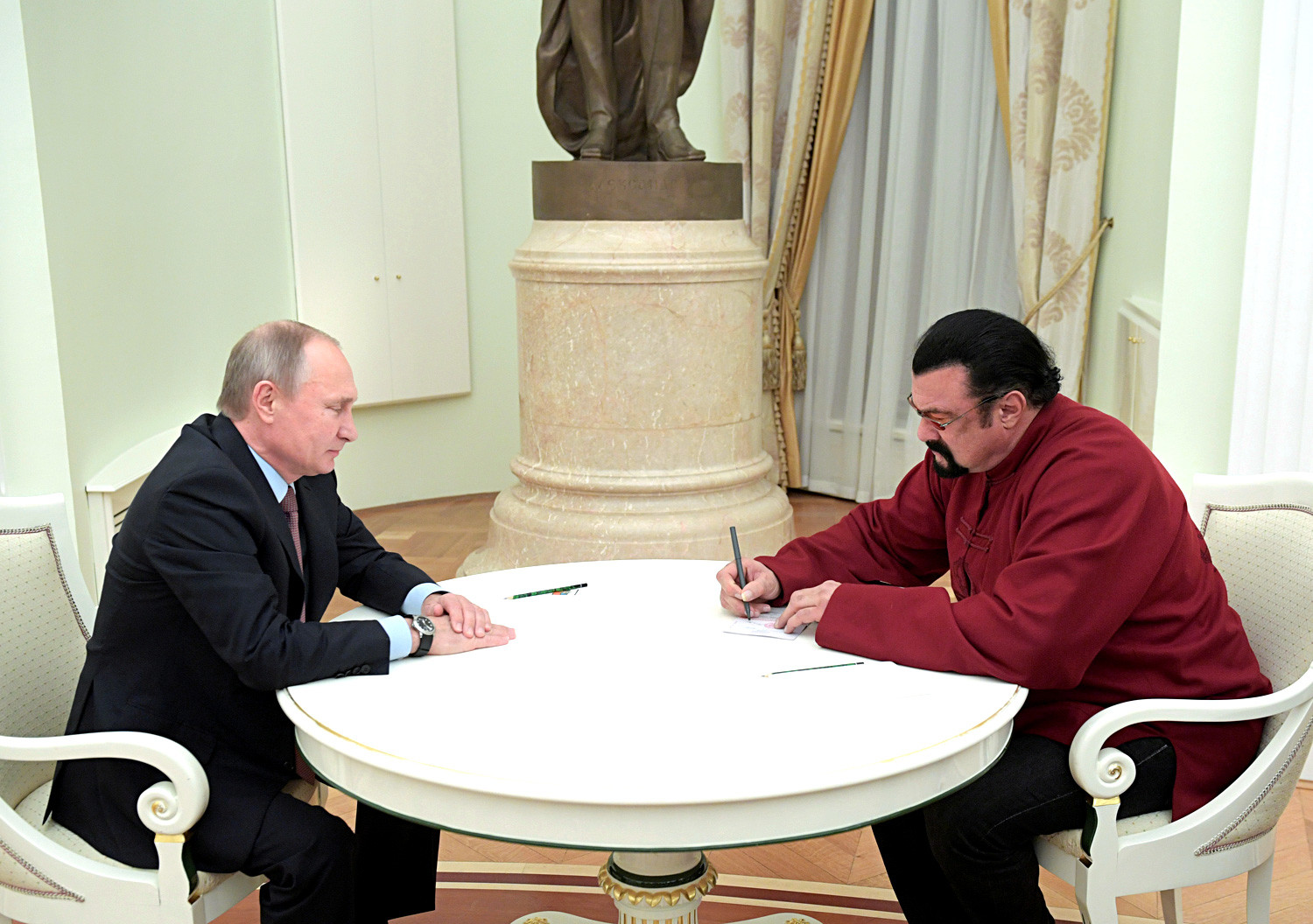 Steven Seagal signs a Russian passport received from Russia's President Vladimir Putin during a meeting at the Kremlin in Moscow, November 25, 2016