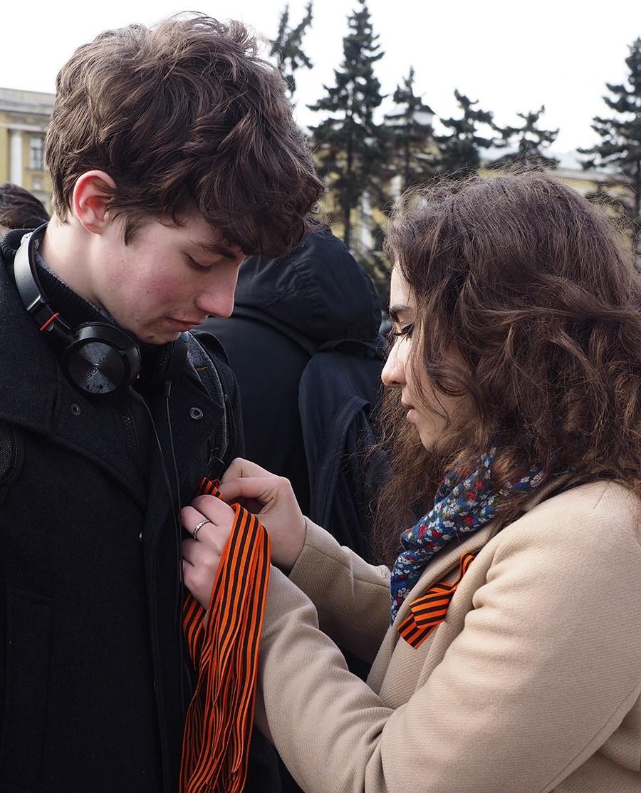Rusija, Sankt Peterburg. Prostovoljka deli trakce sv. Jurija.