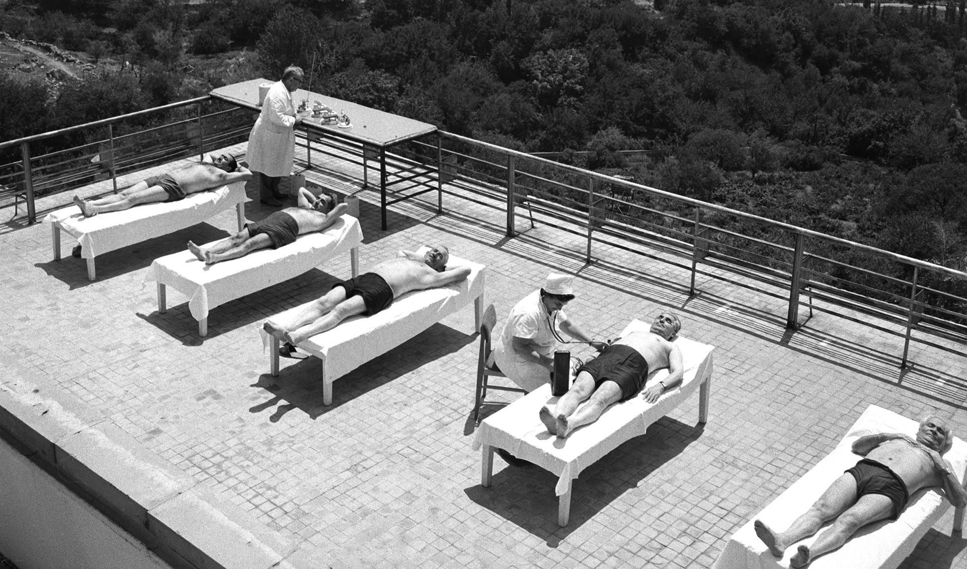 Pacientes de um sanatório tomando sol.