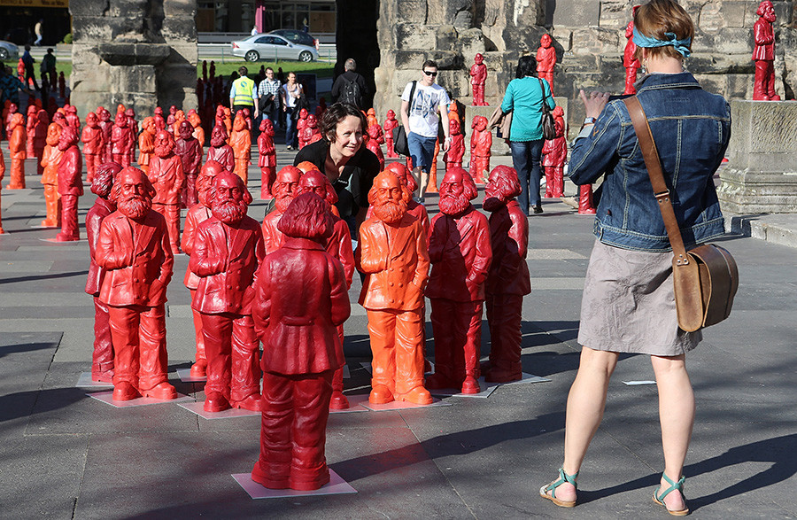 Visitors take photos with some of the 500, one meter tall statues of German political thinker Karl Marx on display on May 5, 2013 in Trier, Germany