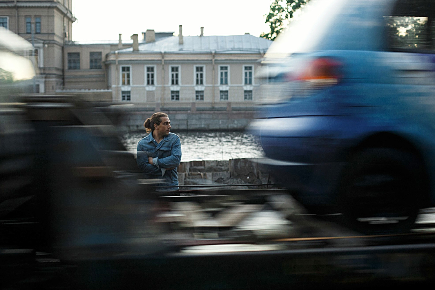 Blurred Motion Of Vehicles Against Man Standing By River Photo Taken In Saint Petersburg, Russia