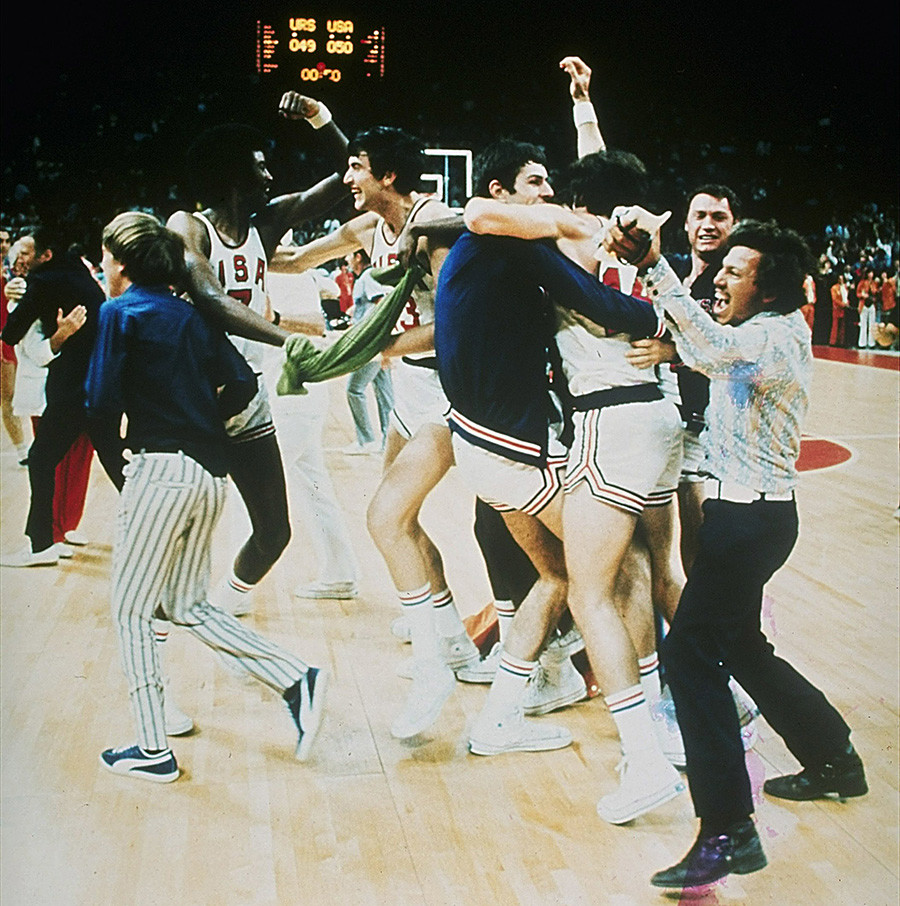 United States basketball team players enjoy a brief moment of elation.