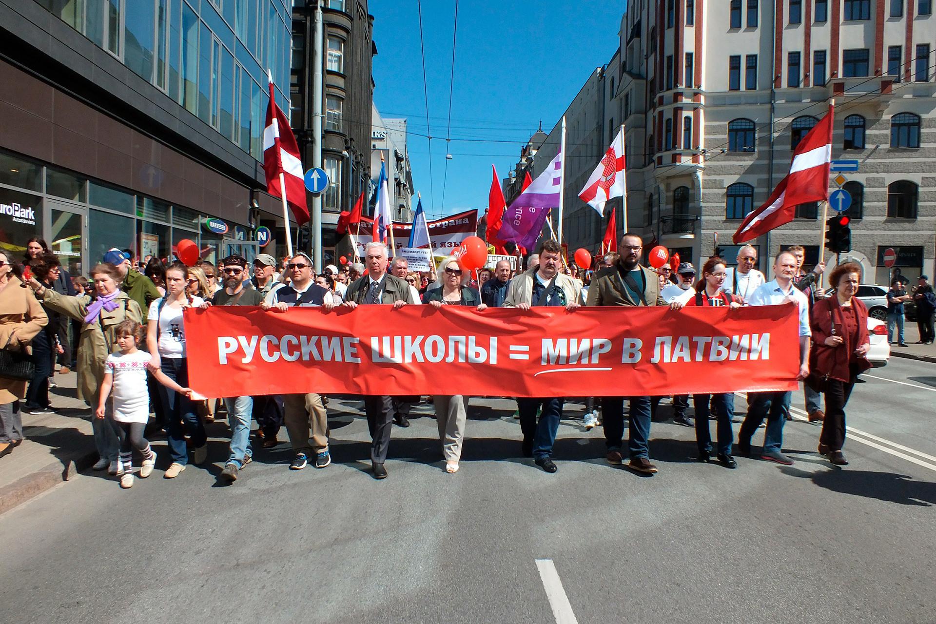 "Masyarakat berunjuk rasa selama Hari Buruh Internasional, 1 Mei 2018, di Riga, ibu kota Latvia, menentang penggunaan penuh bahasa Latvia dalam pendidikan formal dan ""optimalisasi"" sekolah."
