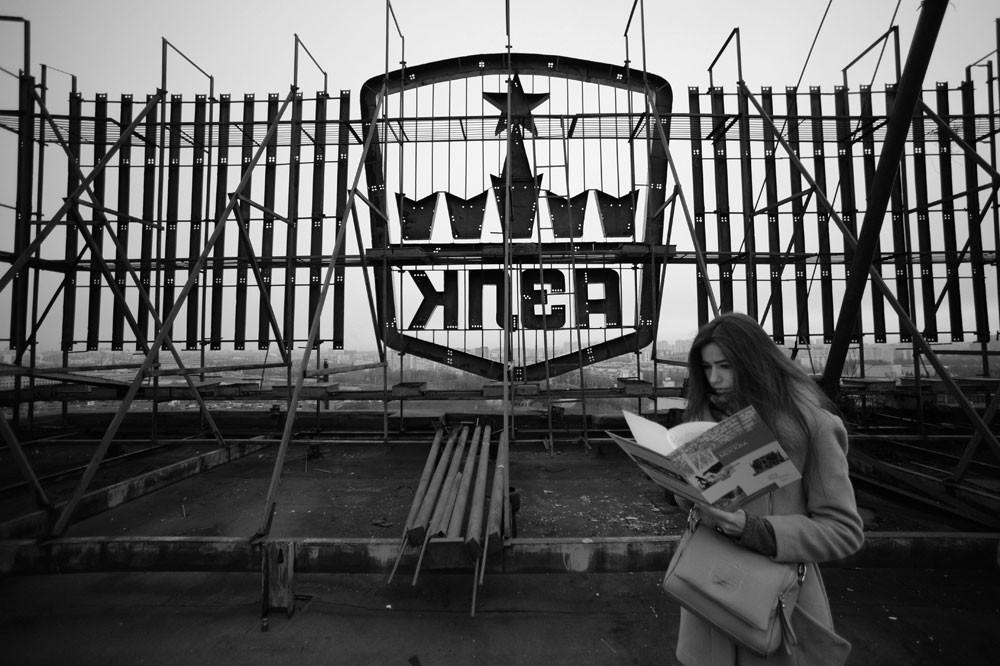 Une femme se tient sur le toit du bâtiment Moskvitch