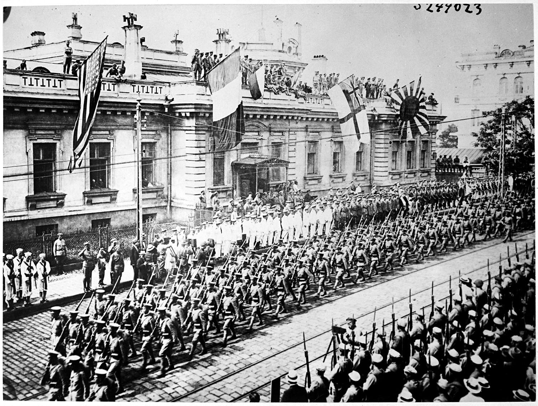 Soldaten und Seeleute aus vielen Ländern stehen vor dem Gebäude der Alliiertenzentrale. Wladiwostok, Russland.