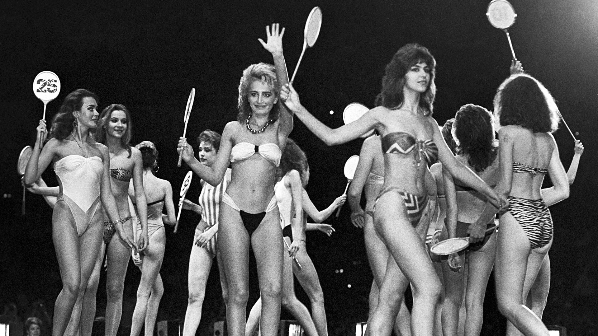 Participants on the runway during swimsuit modeling.